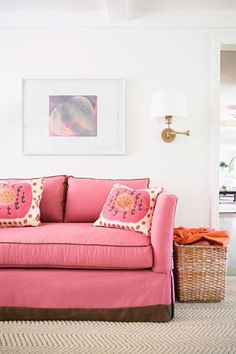 Sweet living room features off-white wall lined with a framed abstract print illuminated by Robert Abbey Koleman Brass Plug-In Swing Arm Wall Lamp over a high-back pink sofa with brown piping and a banded pleated skirt adorned with pink suzani pillows.