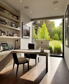 A office in a home in England by Gregory Phillips Architects, that has a floor-to-ceiling window.