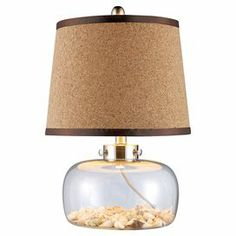 """Showcasing a glass base filled with seashells, this table lamp adds chic coastal style to your decor. Trimmed with a grosgrain ribbon, the cork shade makes a classic finishing touch.   Product: Table lampConstruction Material: Glass, cork and ribbonColor: Tan and clearAccommodates: (1) 60 Watt medium base bulb - not includedDimensions: 20"""" H x 13"""" Diameter"""