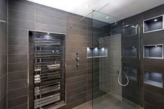 Sleek contemporary bathroom design using LED lit niches and recessed towel rail