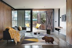 Stonewood by Breathe Architecture - the door, wall? love it       And there's a tiny hippo  sauntering across the room. I love yellow and grey rug!!!!