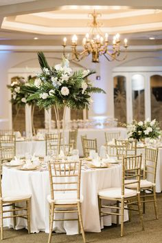 St. Pete Wedding Venue Isla Del Sol   Indoor Ballroom Reception with Blue Uplighting and Gold Chiavari Chairs and Tall Tropical Centerpieces