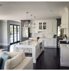 white kitchen with gray accents and contrast dark wood floors White and gray kitchen. White kitchen cabinets with kitchen island featuring antique mirror on sides. Perry Homes. Luxury Interior Design, Home Interior, Kitchen Interior, Interior Paint, Color Interior, Simple Interior, Contemporary Interior, Küchen Design, Home Design