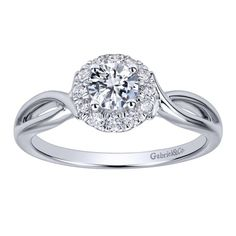 A curved flower engagement ring that has so much to offer! With its simplicity, there also is unique designs on the sides as well as a classic halo around the center stone! This is a gorgeous 14k White Gold Diamond Halo Engagement Ring by Gabriel & Co.