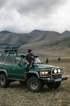 Young man sitting on the old green jeep parked in wild area by Nick Bondarev - Stocksy United Land Cruiser 4x4, Toyota Land Cruiser, Vw Minibus, Green Jeep, Toyota 4x4, Man Sitting, Expedition Vehicle, Road Trip Usa, Old Trucks