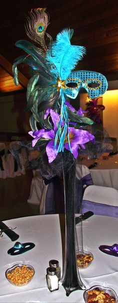 masquerade centerpieces - different color masks worth coordinating flowers and feathers for each table
