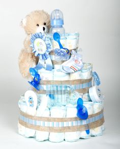 "Step 8: Embellish the diaper cake tiers with themed baby toys, accessories, gifts, and other essentials. We chose to create a ""baby boy"" cake, so all of the embellishments we used were blue.   Note: All items featured in this photo were purchased at Dollar Tree for only $1 (or less) each!"