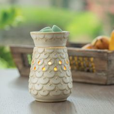 NEW Scalloped Vase Midsize Illumination 13.99  Availability: Allow 3-4 Business Days to Ship  This creamy neutral glaze and scalloped edges make this warmer feel soft and natural.  Uses a soft halogen bulb to create a warm glow and release the scent of your favorite fragrance. Dish is removable and includes the warming bulb.  Ships from MO by UPS