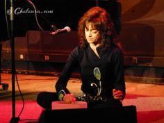 Carmen París sentada en el escenario con blusa y pantalones negros y un detalle floral de un lirio