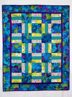 40 x 50 in. lap quilt brightens up a room with brilliant blue and purple Kaffe Fassett floral in alternate blocks and border. Beautiful
