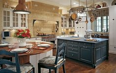 KITCHEN – I like the mix of the dark blue island, the golden colors against the white, makes it interesting.