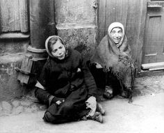 Warsaw, Poland, A Jewish woman sitting with a girl on the sidewalk in the ghetto.  Neither survived