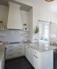 Small u shaped kitchen. this small u-shaped kitchen features a white french hood, stacked white floating shelves, suspended over an induction cooktop with Small U Shaped Kitchens, Small White Kitchens, Kitchen Small, Narrow Kitchen, Beach House Tour, Beach Houses, Beach Cottages, Beach Room Decor, Beach House Decor