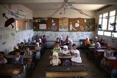 Schoolgirls sit in their classroom at the Saif al-Dawla school as they take part in an art project organised as part of a local initiative to shift the children's minds from the atrocities of the Syrian war