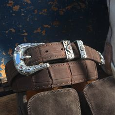 Dress Up your Casual with a elegant handmade sterling silver belt buckle from master silversmith Clint Orms.  Overlay scrolls, rubies and smooth shield make the Collin a timeless masterpiece.  Shown on brown sueded crocodile belt.