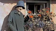 A woman poses next to a windowbox in front of her cottage.Image: Clifton R. Adams / National Geographic.