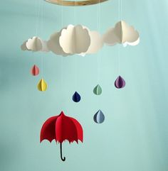 Rainbow-colored raindrops fall from the clouds above a little red umbrella in this adorable 3D mobile. Made of card stock paper, the clouds, raindrops, and umbrella are light enough to be moved by even a gentle breeze. Mobile consists of three 3 dimensional clouds ranging from 2.5 inches to 4.5 inches in width, 6 raindrops, and 1 umbrella measuring 3.5 x 4 inches. Total length of mobile is approximately 14.5 inches.  *This item is made to order, and raindrops and umbrella can be made with…