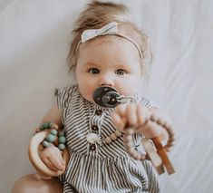 The cutest baby girl with our wooden toys and silicone teethers! #thebabyniche #sootherclip #pacifier #pacifierclip #teether #teething #babyaccessories #babyessentials #babygear #babygift #babyshowergifts #babygirl #babyboy #babyproducts #babygiftideas #toddler #toddlerlife #momlife #babyfashion #babylove #babyaccessory #romper #babygirlclothes #babygirlfashion #bows #babyclothes #babystuff #babystyle Cute Baby Girl, Cute Babies, Baby Shower Gifts, Baby Gifts, Handmade Baby Items, Baby Teethers, Boho Baby, Baby Bows, Baby Girl Fashion