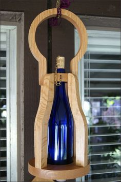 Hanging Candle Lantern with Wooden Basket - Very versatile - Enjoy this lantern hanging, or on your tabletop, and when you need to light your pathway you can carry it.   This is a beautiful decorative handcrafted wooden basket wine bottle candle lantern with a repurposed 750 ml wine bottle. It is beautiful whether or not the candle is lit and is a unique addition to your home decor.