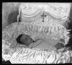 Young boy in a casket. A rosary is in his right hand and a cross is on the underside of the casket's lid. c. 1940