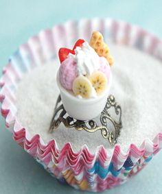 This ring features a miniature cup of handmade frozen yogurt dessert sculpted from air dry clay. it measures about 1.5 cm tall ; and 1 cm in diameter. it is securely attached to an adjustable bronze f