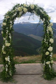 Lush green and white arch on the Vail wedding deck.  Planning by www.IDoWeddingServices.com  Flowers by www.secretgardenvail.com