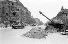 A American soldier inspecting a Panther turret mounted in a fixed position on a West Berlin Street as British vehicles pass by