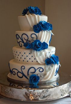 A royal blue wedding cake. With cobalt sugar roses, fondant drapes and cobalt blue scrolls.