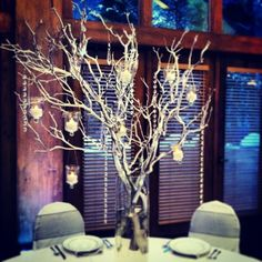 Tall centerpiece with Manzanita, hanging votives and crystals.  #Vail #winter #wedding #flowers