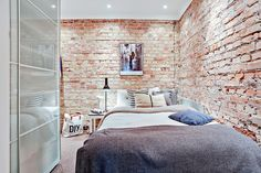 Small bedroom with brick walls