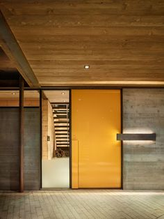 This modern industrial house has a bright yellow front door to greet you and a window gives you a glimpse into the home.