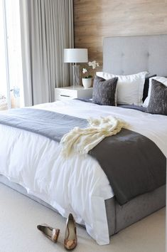 Wood clad wall. Grey and white bedding
