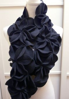 Stay warm and make a statement with this dramatic Dimensional Fleece Rosette Scarf in Black. Seven hand-sewn rosettes made from pill-free fleece make up this beautiful and luxurious scarf. Its so soft and comfortable that you wont want to take it off. The back of the scarf has a