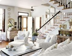 cozy living room...love the wall of various sized mirrors going up the stairs