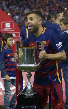 "Barcelona's defender Jordi Alba holds the cup as he celebrates after winning the Spanish ""Copa del Rey"" (King's Cup) final match FC…"