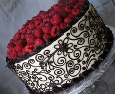 Chocolate fudge cake filled with raspberry and dark chocolate ganache, finished with white chocolate buttercream and dark chocolate piping. Fresh raspberries with a chocolate drizzle adorn the top.