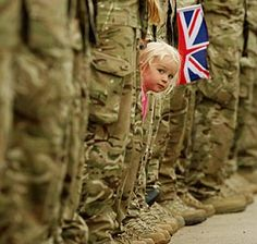 Image: A young girl squeezes between honor guard soldiers to get a glimpse of the Olympic torch on Saturday in Staffordshire, England (© Christopher Furlong/Getty Images)