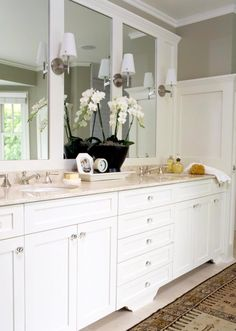 White cabinets are set off with a frosting of marble countertop as well as marble flooring underfoot. A long wall of mirror has been divided with molding and fitted with shaded sconces. An antique runner on the floor includes deeper tones and interesting texture.    Use a tray to corral smaller items on a vanity.  An old-world feel is afforded by glass cabinet knobs.