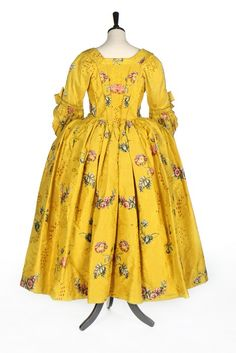 A fine brilliant yellow Spitalfields brocaded silk robe à l'Anglaise, circa 1750. woven with brightly coloured large scale oriental poppies, posies and swags, the ground figured with arabesques and wine silk spotted cartouches, the robe with linen lining to bodice, pleated front robings, double tiered engageants with bows, the hem lined in fine yellow silk; with matching petticoat front panel trimmed with pinked furbelows; and a stomacher trimmed with rosettes and braid (3