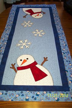 This runner has 2 large snowmen on a light blue background which has been free hand machine quilted. The snowmen has been appliqued on by machine. In the middle are 3 large snowflakes . The border is a blue print with little snowmen on it. The runner measures about 46 inches by 20 1/2 inches wide. It is hand washable. This runner can be used during the whole winter season in your home.