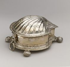 Spice box  W. R., London ca. 1602 - silver. The intricate ornament on this scallop-shaped box reflects the late Elizabethan taste for Antwerp Mannerism; indeed, many specialized workers active in London's goldsmiths' trade came from the Spanish Netherlands. Although shell-shaped boxes such as this one are sometimes referred to as spice boxes, according to early seventeenth-century inventories, they were used for serving sugar, an expensive delicacy.
