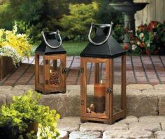 The harmony of elegant wood and sleek black metal makes this tall candle lantern a designers dream come true. The clear glass panels let candlelight s...