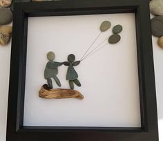 A beautiful and unique handmade pebble art picture of two sisters / best friends standing on driftwood holding balloons and being blown in the wind. This picture is a lovely home decoration and would make a perfect gift. The picture is made using pebbles and driftwood. All materials are carefully placed and fixed with high strength glue onto high quality white linen card. The black frame is approximately 23x 23cm and the frame comes with a wall hanger. Please feel free to message me if you…
