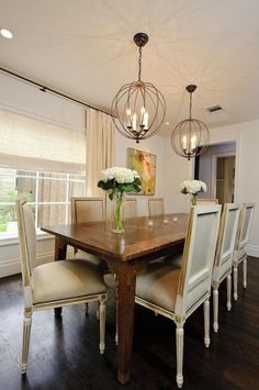 Beautiful dining room with large window dressed in ivory silk drapes layered over ivory roman shade alongside a rustic dining table lined with French square back dining chairs illuminated by a pair of iron sphere shaped pendants.
