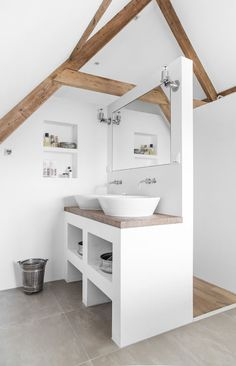 Minimalist bathroom with exposed wooden beams highlighting vaulted ceilings over a white vanity boasting his and her bowl sinks paired with wall-mounted faucets under inset mirror which backs on to hallway alongside open cubbies.