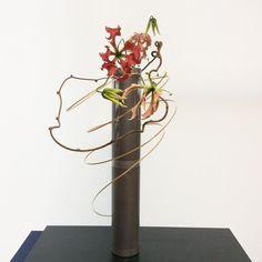 """アトリエ掌 (藤原華峰) on Instagram: """"金属の器に竹ひごと蔓をからませ、グロリオサにつきあってもらう。グロリオサはどこかやんちゃで情が深いと思い込んでいる。花を生けながら、次の仕事の覚悟を決める#ikebana#flower #華道#いけばな#伝統#和物"""" Kiwi Vine, Curly Willow, Cylinder Vase, Ikebana, Bonsai, Vines, Woods, Decorating, Plants"""