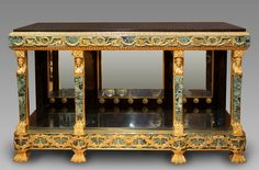 An exceptional Empire style console with four legs shaped in columns topped with gilded bronze caryatids. The console is plated with antique green marble richly ornamented with garlands, laurel and...