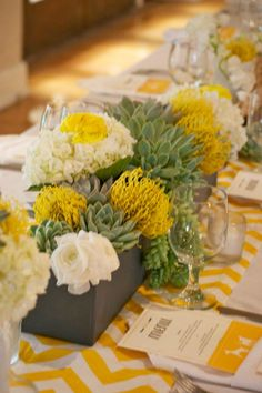 Something like this in some centerpieces but with white and pale pink flowers. The succulents give texture and visual interest plus brings in your nice green!