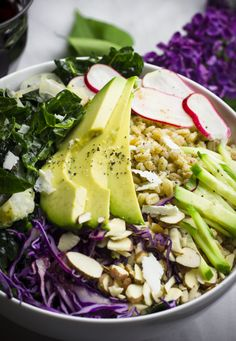 Spring Grain Bowl with farro, radishes, kale, avocados, and more, dressed with a tangy honey-garlic vinaigrette.
