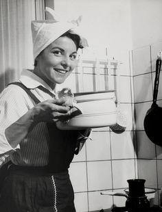 Huishouden, koken. Een huisvrouw met doek om haar hoofd en schort aan houdt glimlachend in een keuken een pan omhoog met twee panlappen. Nederland, 1950-1960.